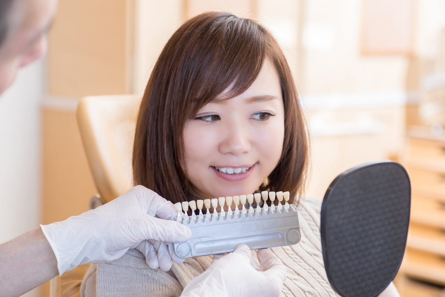 歯の色見本を見る女性